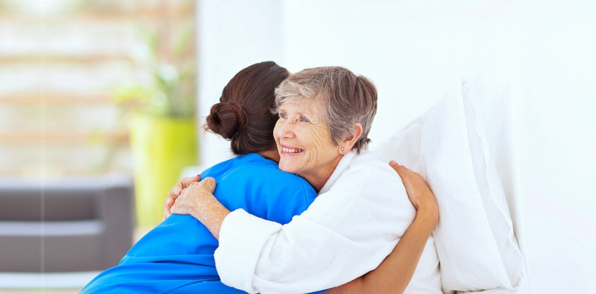 caregiver and senior woman hugging each other